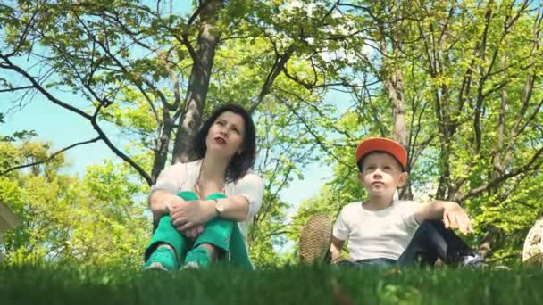 Mom and son are looking into the distance and talking while sitting in the park on the green grass, family holiday