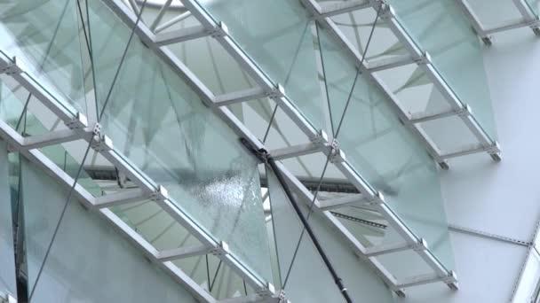 Mytí oken s kartáčem s dlouhou rukojetí, čištění skleněných povrchů na stadionu, pomalý pohyb