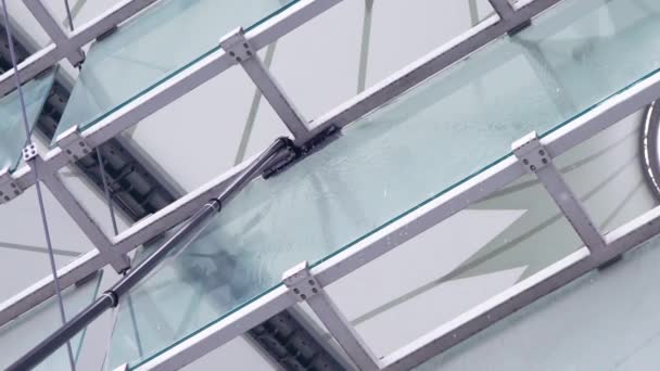 Washing windows with a brush with a long handle, cleaning glass surfaces in the stadium, slow motion