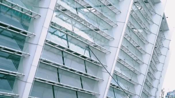 Mytí oken pomocí štětce s dlouhým držadlem, čištění skleněných povrchů na stadionu