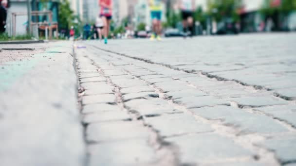 Athletes run along the paved stone road, city marathon, runners legs close-up, sports competition