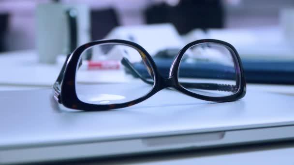 Brýle ležet na přenosný počítač v kanceláři, detail