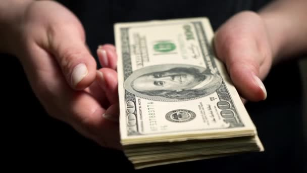 A person takes a hundred-dollar bill from female hands. A woman is holding a pack of American dollars. Currency operations. Loss of money. Bankruptcy. Financial crisis. Playing on the stock exchange.