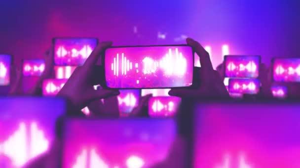 A rajongók okostelefonon rögzítik a videókat. Egy csomó okostelefon. Élő közvetítés. Történeteket. A tömeg koncertet néz, énekel, ugrál. Strobing színpadi lámpák. Zenei fogalom. Boldog emberek néznek egy csodálatos zenei koncertet..