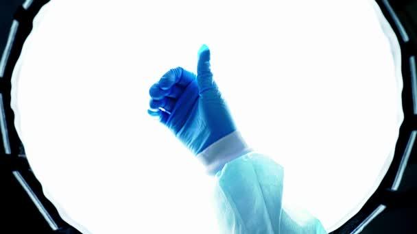 Arzt in blauen Medizinhandschuhen zeigt Daumen hoch. Sieg über die Krankheit. Die Hand einer Krankenschwester, die Menschen während einer Epidemie rettet. Schützen Sie Ihre Hände vor Viren. Weltpandemie, globale Krise. Wie.