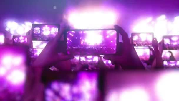 A tömeg koncertet néz, énekel, ugrál. Strobing színpadi lámpák. Boldog emberek. Zenei fogalom. A rajongók okostelefonon rögzítik a videókat. Egy csomó okostelefon. Élő közvetítés. Történetek.