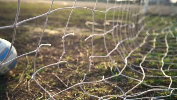 Detailní záběr roztrhané fotbalové sítě. Fotbalový míček skrz síť. Staré fotbalové hřiště u brány. Pouliční sport. Dětská hra. Slunce svítí skrz mřížku. Krize. Fotbal.