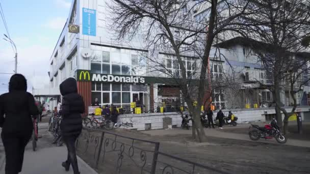 Ukraine, Kyiv, March 22, 2020. Courier delivery service near McDonalds. Glovo couriers pick up orders at McDonalds. Takeaway food for the period of quarantine. Coronavirus epidemic.