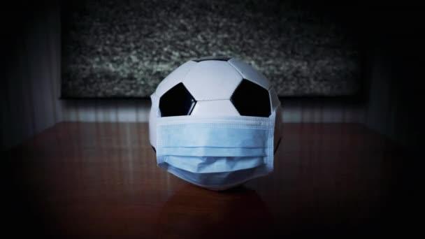 A labda az orvosi maszkban a tévé mellett. A focimeccs lefújva. Világjárvány. Törölje a tömegrendezvényeket. Mondd le, ütemezd át a futball bajnokságot. Koronavírus. TV kép nélkül. Dühös rajongók. Hiba