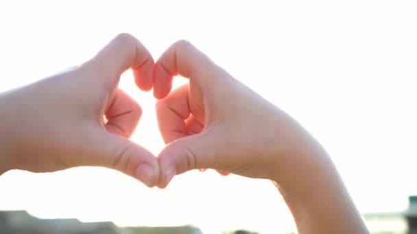 Dítě, které si dělá srdceryvné ruce proti modré obloze, dětské ruce vytvářejí tvar srdce se siluetou západu slunce. Kouzelné paprsky slunce prosvítají mezi prsty. Fantastické jasné světlo. Symbol lásky.