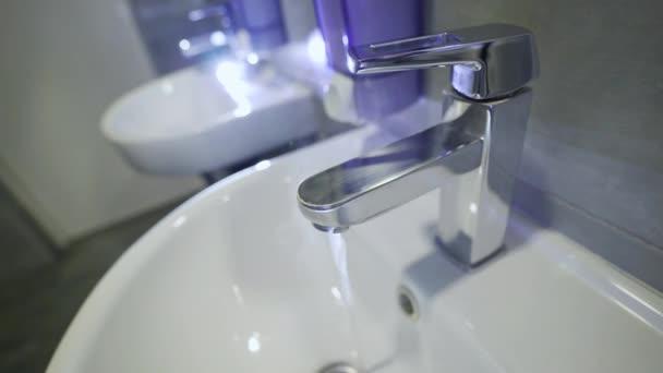 Warmes Leitungswasser. Warmes Wasser fließt aus dem Wasserhahn im Badezimmer. Coronavirus Reiseprävention Händewaschen mit Seife und heißem Wasser. Händehygiene bei Ausbruch des Coronavirus. Schutz durch Händewaschen.
