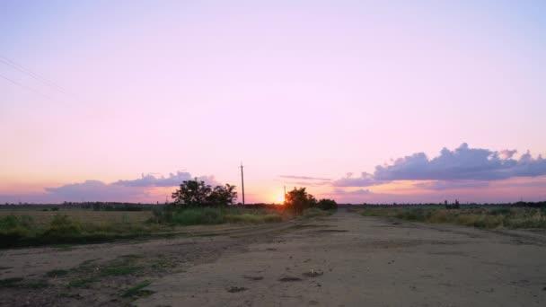 Načasování. Prázdná cesta s ubohým asfaltovým povrchem a výmoly mezi poli. Špatná polní cesta při západu slunce. Východ slunce nad silnicí na poli. Venkov. Stará asfaltová cesta.