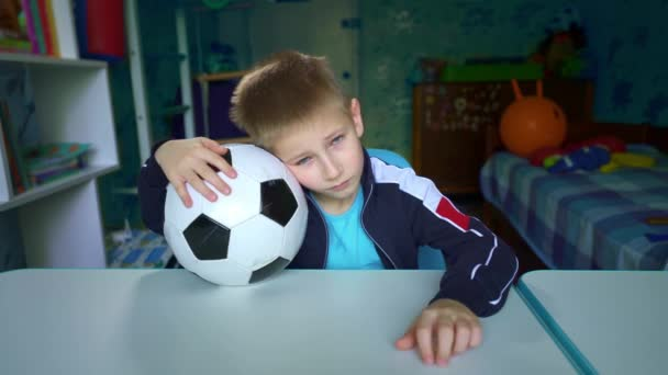 Szomorú gyerek ül egy focilabdával az asztalnál. Egy zaklatott gyerek néz ki az ablakon a karantén alatt. A fiú arról álmodik, hogy focizik a barátaival. Vágytam a meccsre a stadionban. Magányosság.