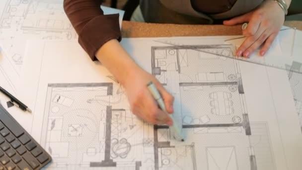 Na pohled shora rukou architekt pracuje na plány
