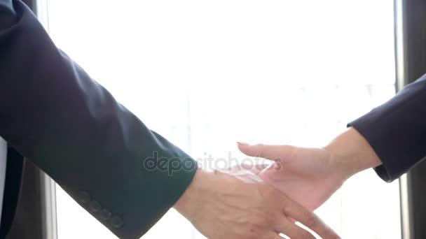 Řešit dohodou. Zpomalený pohyb handshake mezi podnikatelem a podnikatelka