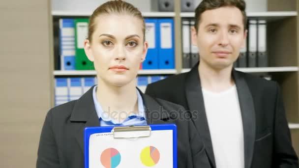 Mladá podnikatelka portrét v interiéru moderních kancelářských a její kolegyně v pozadí