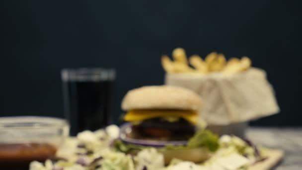 Zoomare su fast food cena composta da hamburger con patatine fritte sulla tavola di legno