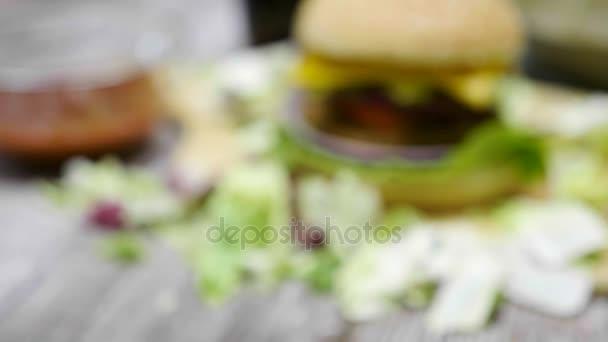 Přiblížit ze zaměření na domácí udělaný hamburger s hranolky na dřevěný stůl