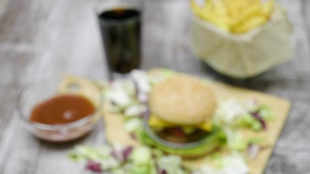 Zvětšení od zaměření přes pohled shora na delicous doma udělaný hamburger s hranolky na dřevěný stůl