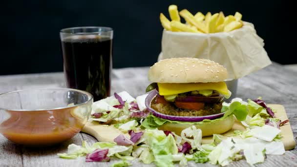 Dolly Shot von Burger, Pommes, Cola und Ketchup auf Holztisch vor schwarzem Hintergrund