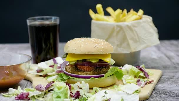 Shot z burger, hranolky, cola a kečup na dřevěný stůl na černém pozadí