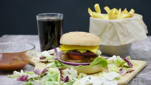Burger, hranolky, cola a kečup na dřevěný stůl na černém pozadí