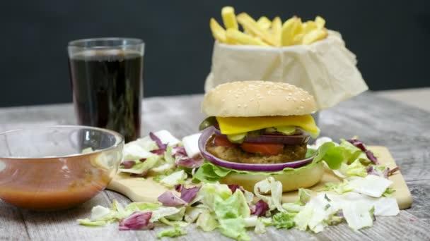 4 k Dolly záběr burger, hranolky, cola a kečup na dřevěný stůl na černém pozadí