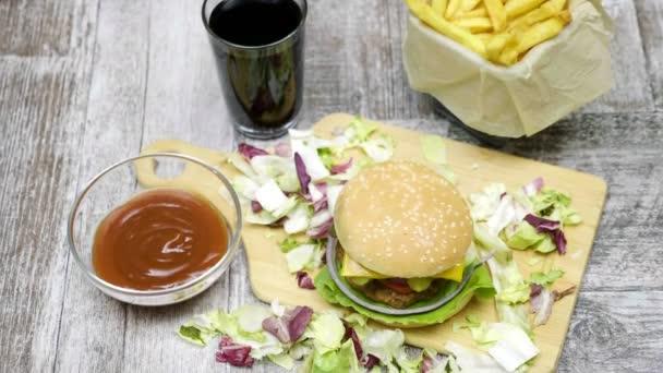 Domácí hamburger s hranolky na dřevěný stůl