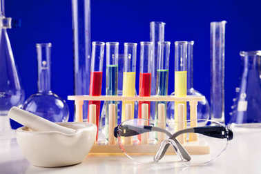 Chemistry lab set on a table with protective eyeglasses over blu