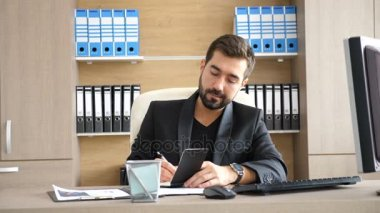 Young businessman in his office taking notes in a paper notebook