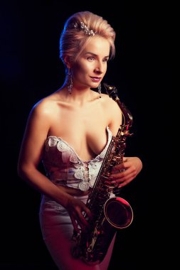 Sexy saxophone woman player with her instrument in studio photo