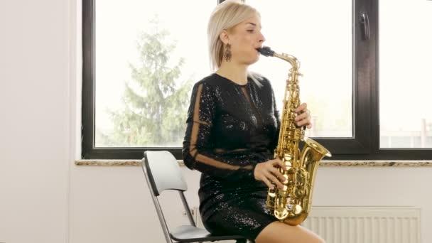 Szaxofonos gyönyörű nő játszik a szaxofon, a nappaliban