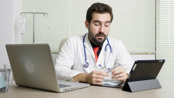 Young doctor in his office talking to the camera