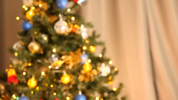 Zooming in from out of focus to close up on Christmas tree with garlands