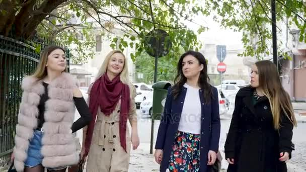 Gruppe fröhlicher Freundinnen spaziert durch die Altstadt einer Stadt