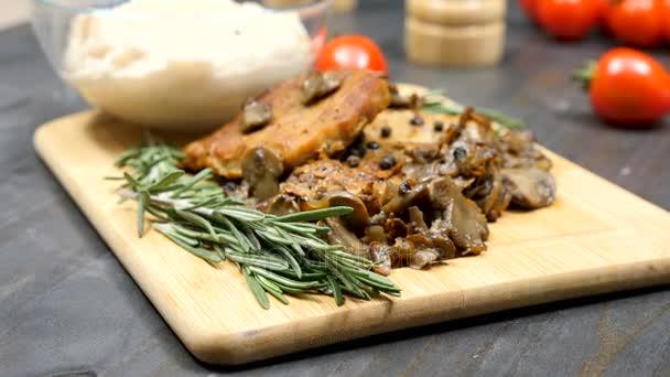 Dolly záběry paralaxy chutné vařené vepřové kotlety s grilovanými žampiony, fazolové těstoviny vedle koření oregáno a cherry rajčátky