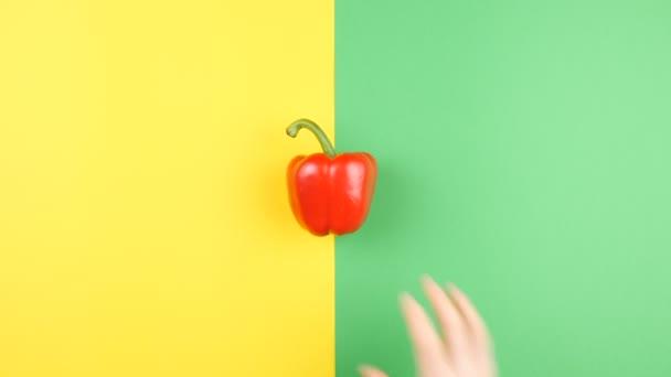 Felülnézet kéz, édes pirospaprika forgalomba két színes háttérrel