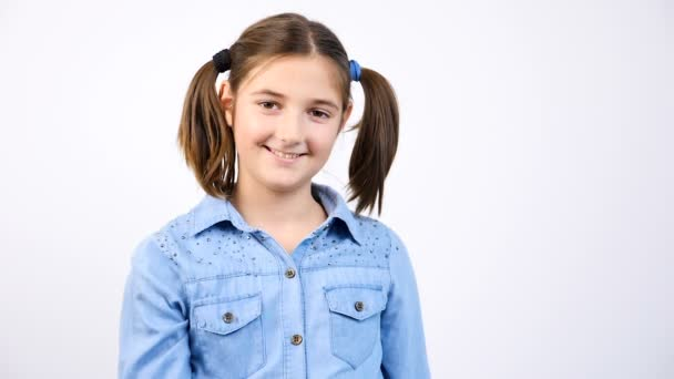 Roztomilá holčička ukazuje palec nahoru znamení na šedém pozadí