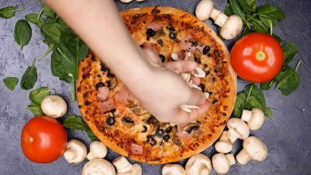 Zpomalený pohyb rukou koření pizza s houbami