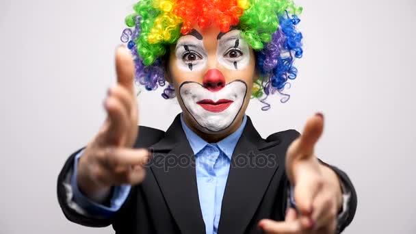 Bohóc nő öltöny és színes paróka, hogy fegyvert jelek kezében