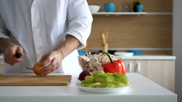 Vaření v moderní kuchyni dělené cibule na dřevěný stůl