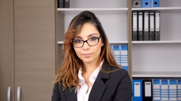 Krásná bruneta podnikatelka v úřadu se usmívá na kameru