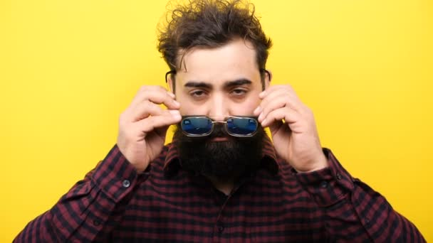Smiling long bearded hipster puts his glasess on the face