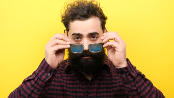 Smiling bearded hipster on yellow background