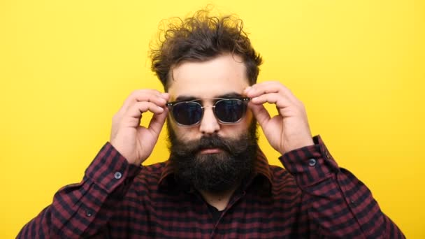 bearded hipster lowers his sunglasses on yellow background