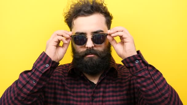 Long bearded hipster lowers his sunglasses