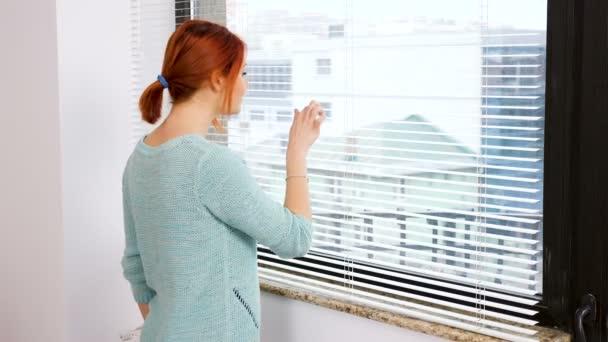 Žena lookis za kuchyňským oknem