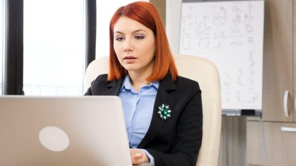 Podnikatelka, psaní na notebooku a při pohledu na grafy