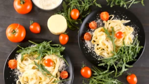 Healthy and delicious tagliattele pasta in two black plates