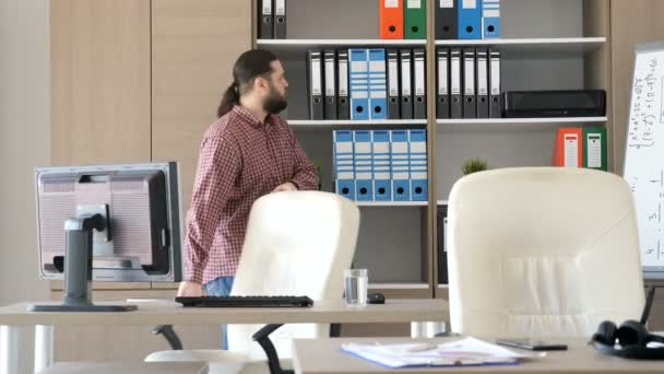 Man entering the office and starts pulling files from the cabinet